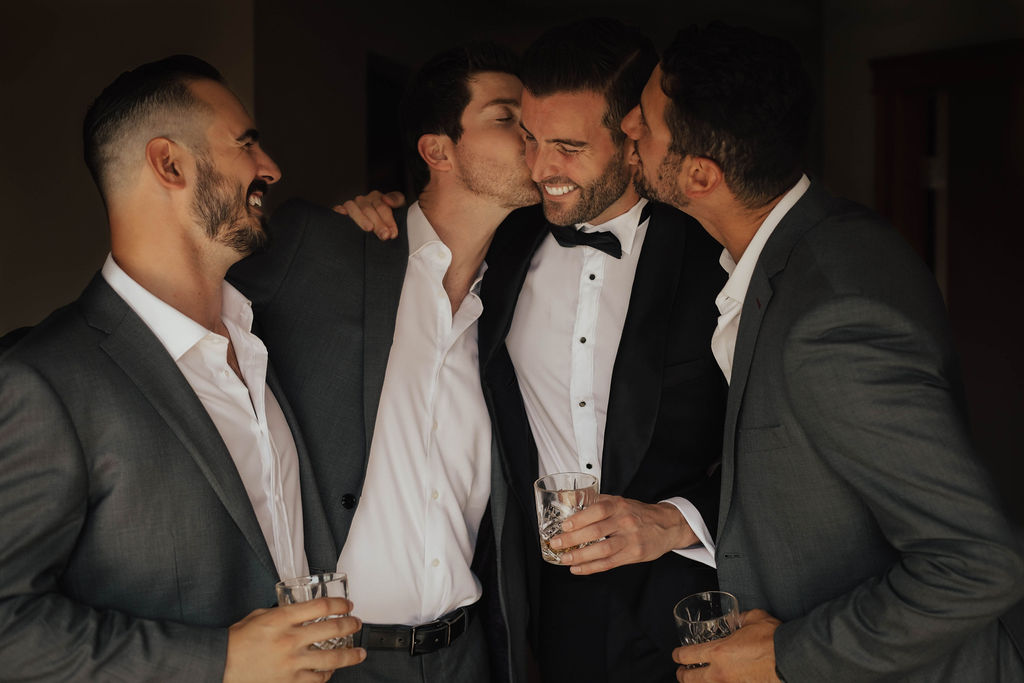 The groom is congratulated by groomsmen in suits with whiskey