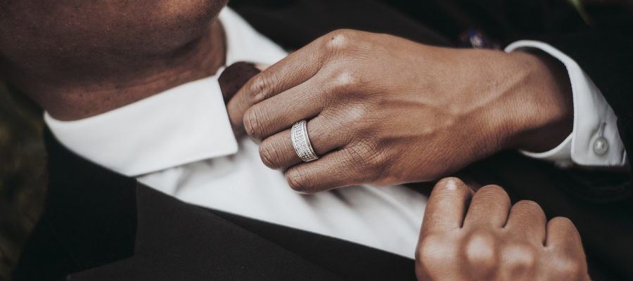 A man adjusts his tie on his wedding day wearing a pave diamond band