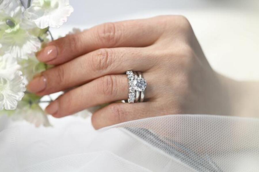 A bride wearing an Eternity diamond ring as part of a wedding set with white flowers