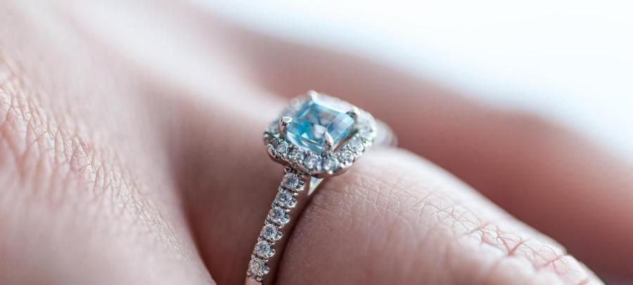 A blue sapphire ring on a hand