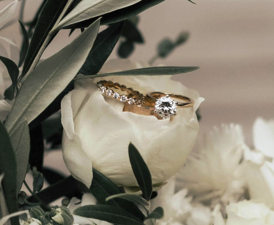A set of wedding bands on white flowers