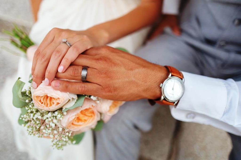A couple rest their hands on a bouquet of flowers